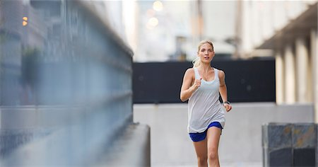 Woman running through city streets Stock Photo - Premium Royalty-Free, Code: 6113-07790830