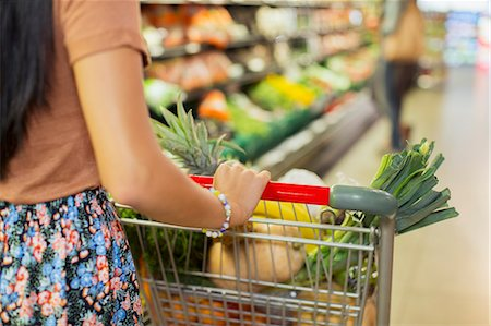 Close up of woman pushing full shopping cart in grocery store Stock Photo - Premium Royalty-Free, Code: 6113-07790948