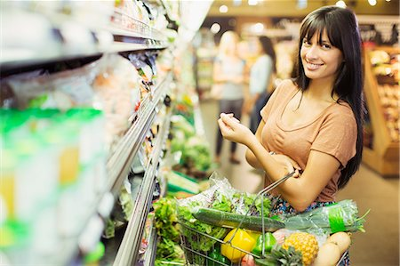 Woman carrying full shopping basket in grocery store Stock Photo - Premium Royalty-Free, Code: 6113-07790953