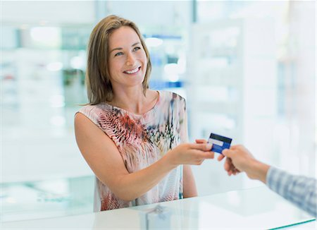 Woman paying with credit card in drugstore Stock Photo - Premium Royalty-Free, Code: 6113-07790951
