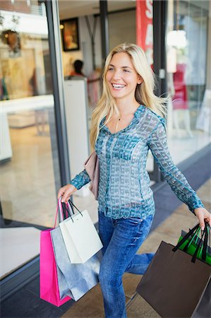 shopping mall - Woman carrying shopping bags in shopping mall Stock Photo - Premium Royalty-Free, Code: 6113-07790952
