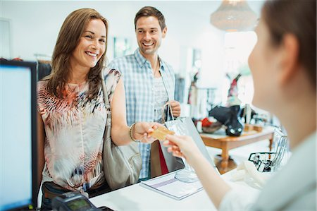 Couple paying with credit card in clothing store Stock Photo - Premium Royalty-Free, Code: 6113-07790955