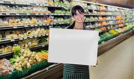 Clerk holding blank card in produce section of grocery store Stock Photo - Premium Royalty-Free, Code: 6113-07790975