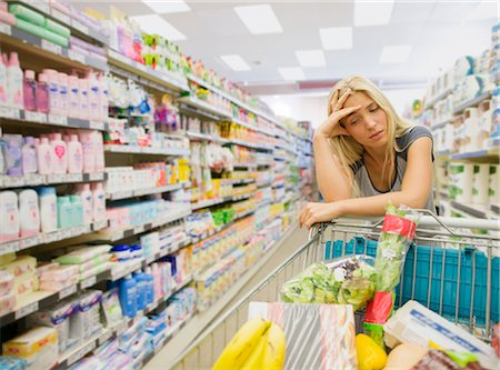 Frustrated woman pushing shopping cart in grocery store Stock Photo - Premium Royalty-Free, Code: 6113-07790988