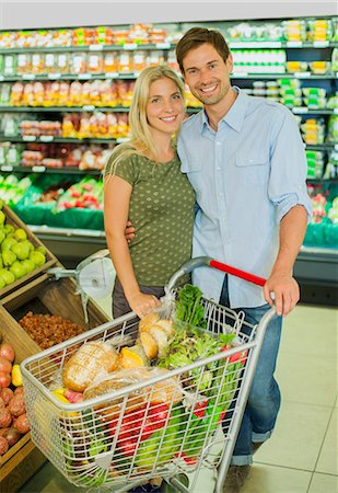 Couple smiling with full shopping cart in grocery store Stock Photo - Premium Royalty-Free, Code: 6113-07790990