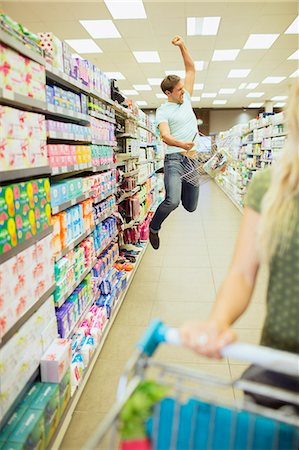 Man jumping for joy in grocery store Stock Photo - Premium Royalty-Free, Code: 6113-07790997