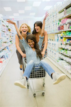 Women playing with shopping cart in grocery store Stock Photo - Premium Royalty-Free, Code: 6113-07790933