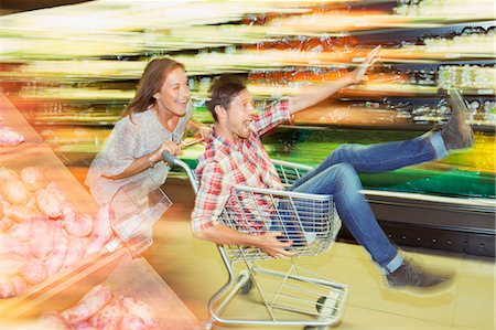 Blurred view of couple playing with shopping cart in grocery store Stock Photo - Premium Royalty-Free, Code: 6113-07790934