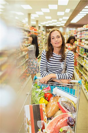 Woman pushing full shopping cart in grocery store Stock Photo - Premium Royalty-Free, Code: 6113-07790936
