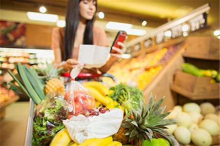 retail store - Woman checking shopping list in grocery store Stock Photo - Premium Royalty-Free, Code: 6113-07791041