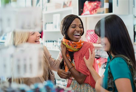 funny looking people - Women laughing together in clothing store Stock Photo - Premium Royalty-Free, Code: 6113-07791048