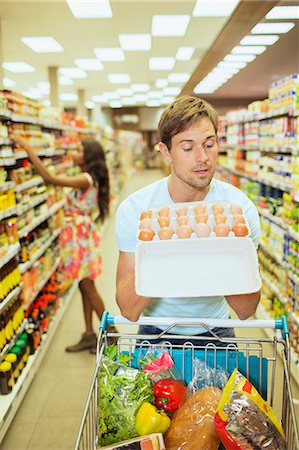 Man examining carton of eggs in grocery store Stock Photo - Premium Royalty-Free, Code: 6113-07791049