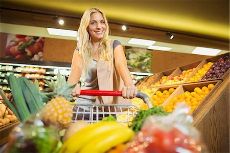 Woman pushing full shopping cart in grocery store Stock Photo - Premium Royalty-Free, Code: 6113-07791053