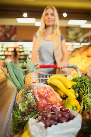 Woman pushing full shopping cart in grocery store Stock Photo - Premium Royalty-Free, Code: 6113-07791051