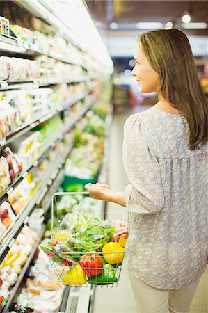 Woman carrying full shopping basket in grocery store Stock Photo - Premium Royalty-Free, Code: 6113-07791056
