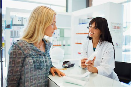 Woman discussing product with pharmacist in drugstore Stock Photo - Premium Royalty-Free, Code: 6113-07791066
