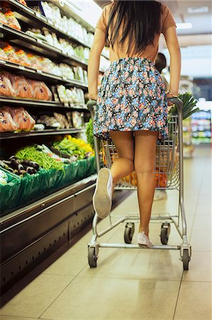 Woman playing on shopping cart in grocery store Stock Photo - Premium Royalty-Free, Code: 6113-07791070