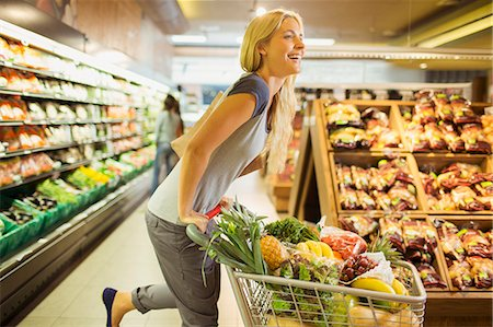 Woman playing with shopping cart in grocery store Stock Photo - Premium Royalty-Free, Code: 6113-07791080