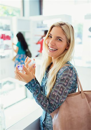 smelling - Woman trying on perfume in drugstore Stock Photo - Premium Royalty-Free, Code: 6113-07791012