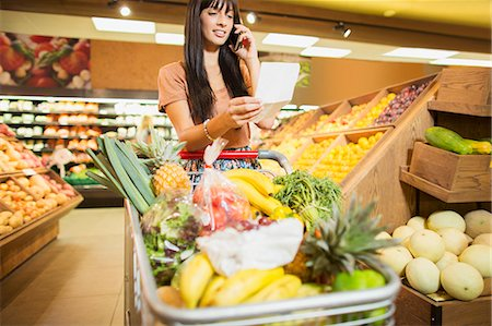 Woman talking on cell phone in grocery store Stock Photo - Premium Royalty-Free, Code: 6113-07791019