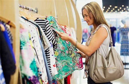 Woman checking price tags while shopping in clothing store Stock Photo - Premium Royalty-Free, Code: 6113-07791025