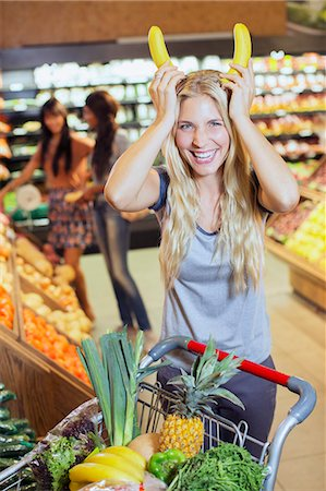 Woman playing with bananas while shopping in grocery store Stock Photo - Premium Royalty-Free, Code: 6113-07791035