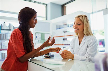 Woman discussing skincare product with pharmacist in drugstore Stock Photo - Premium Royalty-Free, Code: 6113-07791146