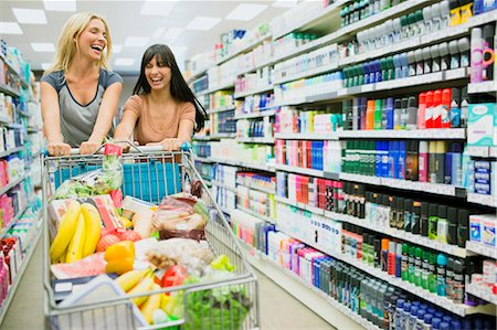 Women pushing full shopping cart together in grocery store Stock Photo - Premium Royalty-Free, Code: 6113-07791150