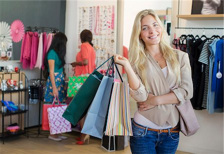 Woman carrying shopping bags in clothing store Stock Photo - Premium Royalty-Free, Code: 6113-07791152