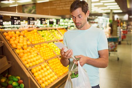 domestic life - Surprised man reading receipt in grocery store Stock Photo - Premium Royalty-Free, Code: 6113-07791155