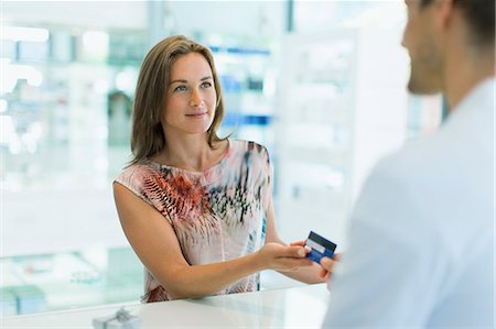 Woman paying with credit card in drugstore Stock Photo - Premium Royalty-Free, Code: 6113-07791159