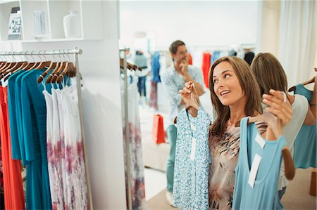Man helping girlfriend pick dresses in clothing store Stock Photo - Premium Royalty-Free, Code: 6113-07791160