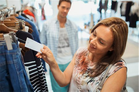 Woman checking tag while shopping in clothing store Stock Photo - Premium Royalty-Free, Code: 6113-07791165