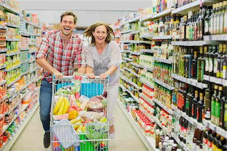 Couple playing with shopping cart in grocery store aisle Stock Photo - Premium Royalty-Free, Code: 6113-07791171