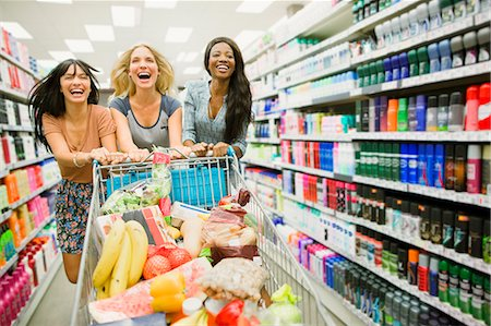 Women playing with shopping cart in grocery store aisle Stock Photo - Premium Royalty-Free, Code: 6113-07791177