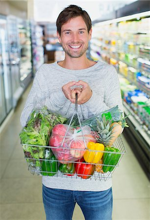 food - Man holding full shopping basket in grocery store Stock Photo - Premium Royalty-Free, Code: 6113-07791176