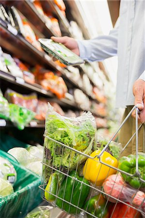 Close up of man holding full shopping basket in grocery store Stock Photo - Premium Royalty-Free, Code: 6113-07791178