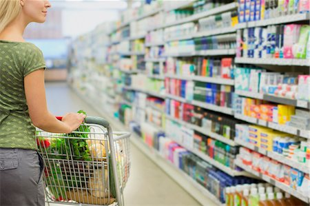 Woman pushing full shopping cart in grocery store Stock Photo - Premium Royalty-Free, Code: 6113-07791181