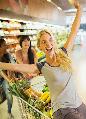 Women playing on shopping cart in grocery store Stock Photo - Premium Royalty-Free, Code: 6113-07791189