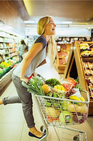 Woman playing on shopping cart in grocery store Stock Photo - Premium Royalty-Free, Code: 6113-07791195