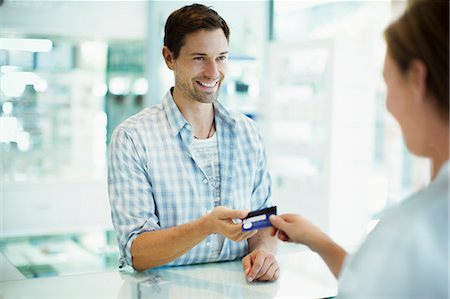 Man paying with credit card in drugstore Stock Photo - Premium Royalty-Free, Code: 6113-07791117