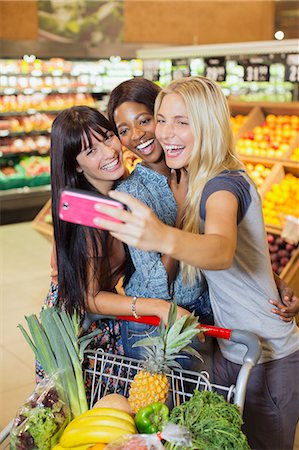 Women taking picture together in grocery store Stock Photo - Premium Royalty-Free, Code: 6113-07791114