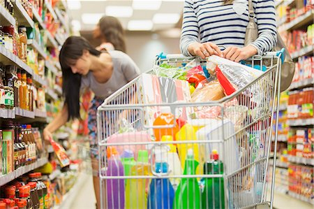 Woman pushing full shopping cart in grocery store Stock Photo - Premium Royalty-Free, Code: 6113-07791120