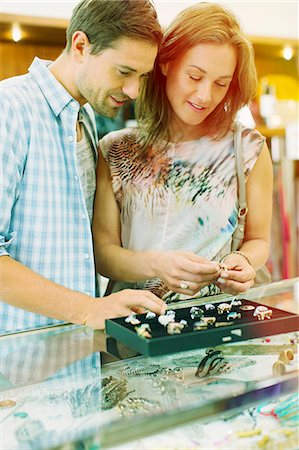 Couple examining jewelry together in store Stock Photo - Premium Royalty-Free, Code: 6113-07791128