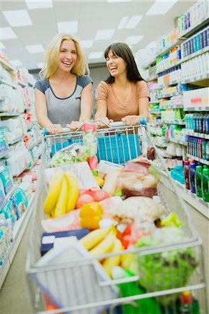 Women pushing full shopping cart together in grocery store Stock Photo - Premium Royalty-Free, Code: 6113-07791206