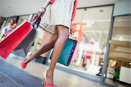 shopping mall - Low angle view of woman carrying shopping bags in shopping mall Stock Photo - Premium Royalty-Free, Code: 6113-07791218