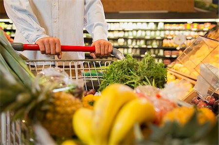 Close up of man pushing full shopping cart in grocery store Stock Photo - Premium Royalty-Free, Code: 6113-07791227