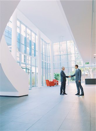 Businessmen shaking hands in office building Stock Photo - Premium Royalty-Free, Code: 6113-07791355