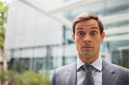 pressure - Businessman with eyebrows raised outside office building Stock Photo - Premium Royalty-Free, Code: 6113-07791397