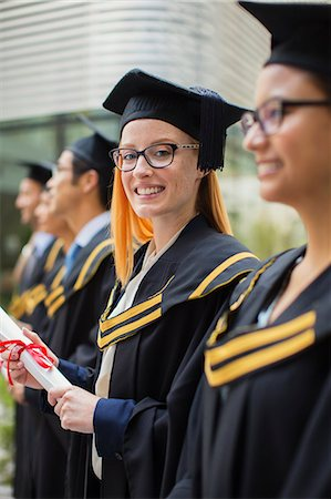 Woman in cap and gown standing with colleges Stock Photo - Premium Royalty-Free, Code: 6113-07791483